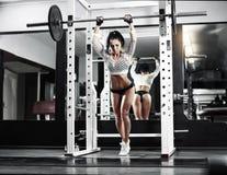 Ung sexig brunettflicka i göra för idrottshall som är satt med skivstången royaltyfri foto