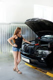 Ung sexig brunettmekaniker i kontrollerad skjorta i garage Auto di Royaltyfri Bild