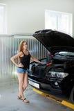 Ung sexig brunettmekaniker i kontrollerad skjorta i garage Auto di Royaltyfri Fotografi