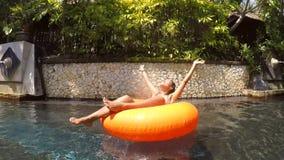 Ung sexig flicka i bikini som kopplar av på röret i den lata floden Waterpark för simbassäng Slowmotion HD arkivfilmer