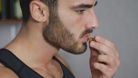 Ung sexig idrotts- man som äter mandlar Arkivbilder