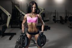 Ung sexig konditionbrunettkvinna i idrottshallen som gör övningar royaltyfri foto