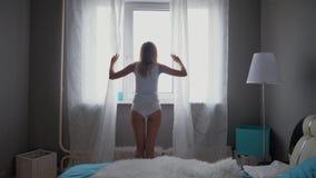 Ung sexig kvinna, i gardin och att se för underkläder öppen ut ur fönster arkivfilmer