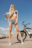 Ung sexig kvinna med cykeln utomhus arkivfoto
