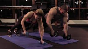 Ung sexig kvinna och muskulös man som gör övning med hantlar på golvet stock video