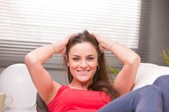 Ung sexig kvinna som ler på en soffa arkivfoton