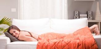 Ung sexig kvinna som ler på en soffa royaltyfri bild