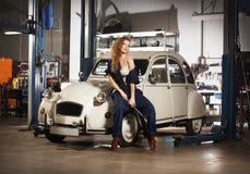 Ung sexig kvinna som reparerar en retro bil arkivbilder