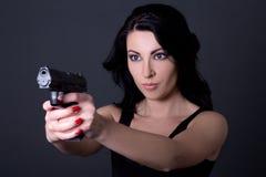 Ung sexig kvinna som siktar med vapnet över grå färger arkivbild