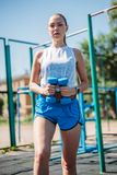 Ung sexig kvinna som utomhus utarbetar med hantlar i idrottshall arkivbild
