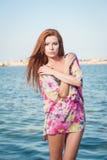 Ung sexig röd hårflicka i den mångfärgade blusen som poserar på stranden Den sinnliga attraktiva kvinnan med långt hår, sommar sk Arkivfoton