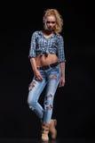 Ung sexig tillfällig kvinna, i jeans och att posera för skjorta Royaltyfri Foto