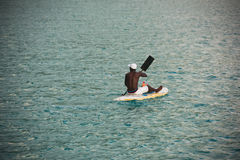 Ung Seychellois man på en surfingbräda i havet Royaltyfri Fotografi