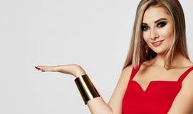 Ung sinnlig härlig kvinna som pekar den öppna handen med textutrymme i röd klänning för mode och stort guld- armband royaltyfria bilder