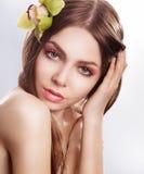 Ung sinnlig kvinna för skönhetframsida med orchidblomman fotografering för bildbyråer