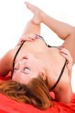 Ung sinnlig kvinna på en röd torkduk arkivfoto