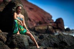 Ung sinnlig kvinna som poserar på den vulkaniska stranden i sommar Arkivfoton