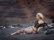 Ung sinnlig kvinna som poserar på den vulkaniska stranden i sommar Royaltyfri Foto