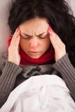 Ung sjuk flicka som ligger i säng med huvudvärk Arkivbild