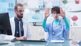 Ung sjuksköterska som bär AR-skyddsglasögon och talar med hennes professor arkivfilmer
