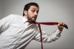 Ung skäggig man med att dra för tie som är självt Fotografering för Bildbyråer