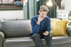 Ung skäggig man som använder smartphonen som sitter på soffan f arkivfoto