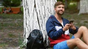 Ung skäggig man som skriver ett meddelande av mobiltelefonen som sitter under trädet Studenten som pratar i, parkerar stock video