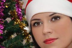 Ung skönhet som ler den santa kvinnan nära julgranen Royaltyfri Fotografi