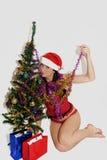 Ung skönhet som ler den santa kvinnan nära julgranen Fotografering för Bildbyråer