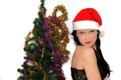 Ung skönhet som ler den santa kvinnan nära julgranen Arkivfoto