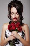 Ung skönhet som luktar buketten av röda rosor. Nöje & harmoni Royaltyfria Bilder