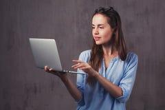 Ung skönhetbrunettkvinna med bärbara datorn royaltyfri fotografi