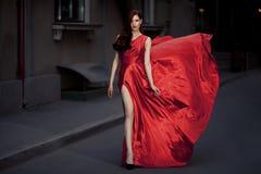 Ung skönhetkvinna i fladdrande röd klänning Royaltyfria Foton