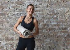 Ung skinheadkvinnlig med mattt anseende för yoga nära väggen arkivbilder