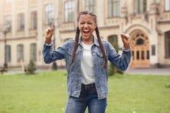 Ung skolflicka i jeans som står på skolgården som skriker irriterade stängda ögon arkivbild