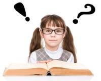Ung skolflicka med den exponeringsglas lästa boken Isolerat på vit royaltyfria foton