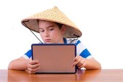 Ung skolpojke som studerar i en kinesisk hatt royaltyfri fotografi