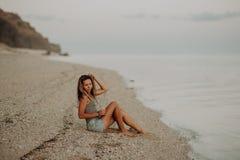 Ung slank härlig kvinnaflicka på solnedgångstranden, indie stil bakgrund föder upp den steniga stenstrukturen för rocken fotografering för bildbyråer