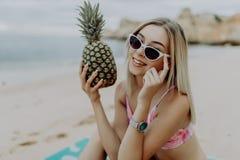 Ung slank kvinna i bikinin och solglasögon som rymmer ny ananas på havsstranden arkivbild