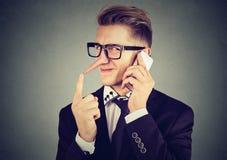 Ung slug man med den långa näsan som talar på mobiltelefonen Lögnarebegrepp fotografering för bildbyråer