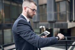 Ung smart affärsman i dräkt som kontrollerar Smart-klockan Arkivfoto