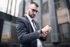 Ung smart affärsman i dräkt som kontrollerar Smart-klockan Royaltyfria Foton