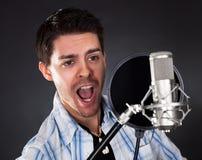 Ung sångare med mikrofonen Fotografering för Bildbyråer