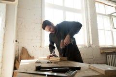 Ung snickare som gör träverk i snickeri Arkivfoton