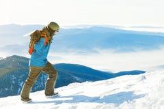 Ung snowboarder i hjälm som går till det mycket bästa av ett berg på den guld- timmen Royaltyfria Bilder