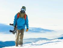 Ung snowboarder i hjälm som upptill går av ett berg på den guld- timmen med hans snowboard i hand Royaltyfria Foton