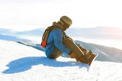 Ung snowboarder i hjälmen som upptill sitter av ett berg och drar åt hans band på den guld- timmen Royaltyfri Bild