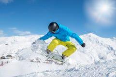 Ung snowboarder i skyddande kugghjulbanhoppning Royaltyfri Foto