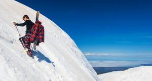 Ung snowboarder som upp klättrar lutningen Fotografering för Bildbyråer
