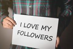 Ung social massmediainfluencer i plädskjortan som rymmer ett plakat med text: JAG ÄLSKAR MINA ANHÄNGARE! royaltyfria bilder